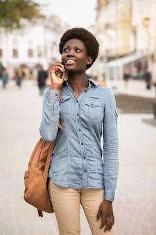 Telefono donna nera giovane a piedi