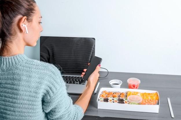 Telefono femminile della tenuta della mano con lo schermo dell'alimento di consegna di app e la radio dell'ufficio del posto di lavoro del computer portatile