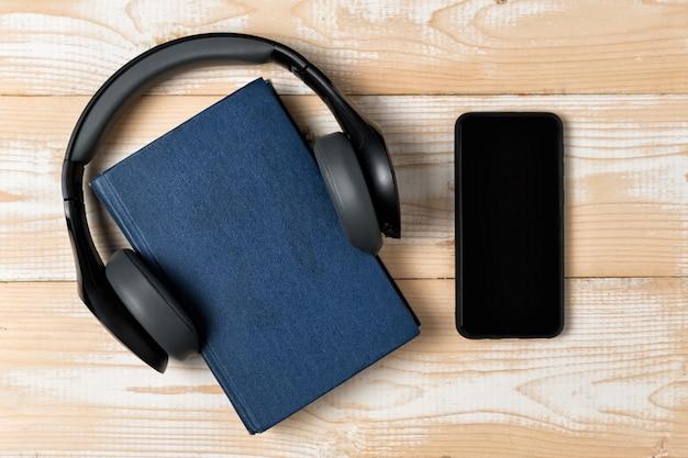 Telefono, libro e auricolari su uno sfondo in legno chiaro. concetto di e-book e audiolibri. vista dall'alto