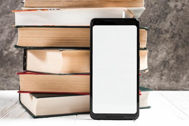Telefono mobile bianco della visualizzazione dello schermo in bianco davanti al libro impilato sulla tavola