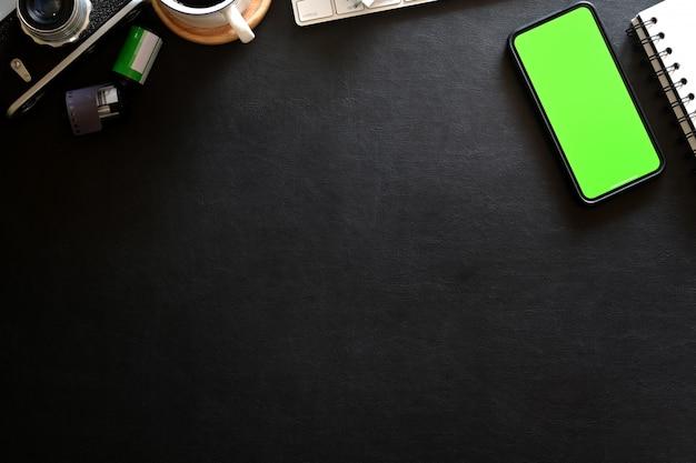 Telefono mobile del modello sul posto di lavoro del fotografo con fondo scuro di cuoio
