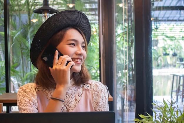 Telefono parlante sorridente della ragazza asiatica in caffè
