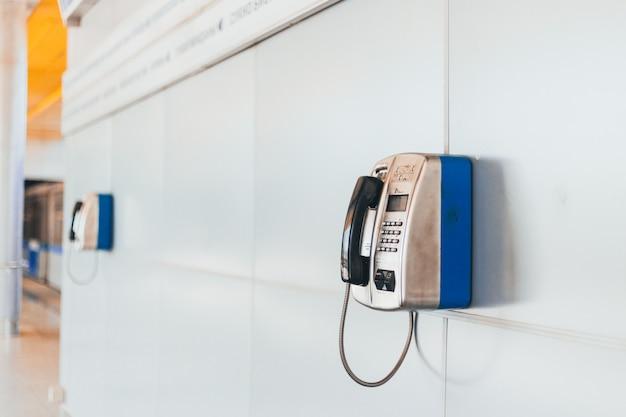 Telefono pubblico stazionario del primo piano alla stazione della metropolitana nel pomeriggio