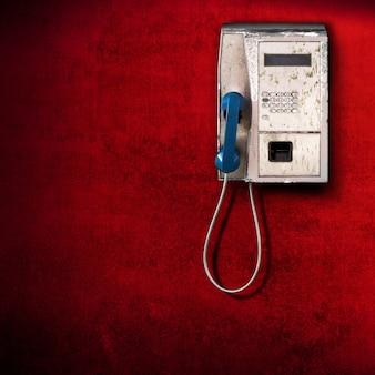 Telefono pubblico su sfondo rosso