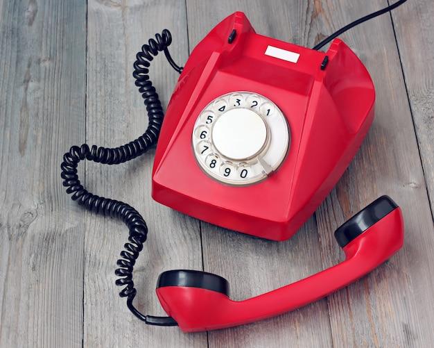 Telefono rosso rotante sganciato su una piattaforma di legno.