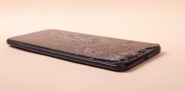 Telefono rotto su uno smartphone di vetro dell'esposizione rotto primo piano beige del fondo.