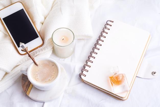 Telefono, tazza di caffè bianca e candela con il taccuino sul letto bianco e plaid, luce accogliente di mattina.