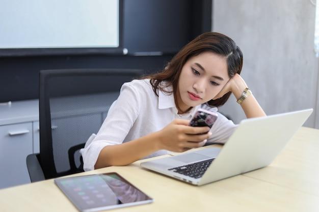 Telefono usando asiatico della donna di affari per celling e mandare un sms sul suo telefono cellulare