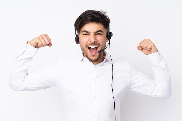 Telemarketer arabian uomo che lavora con un auricolare isolato su bianco per celebrare una vittoria