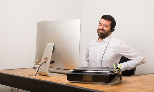 Telemarketer uomo in un ufficio che soffre di mal di schiena per aver fatto uno sforzo