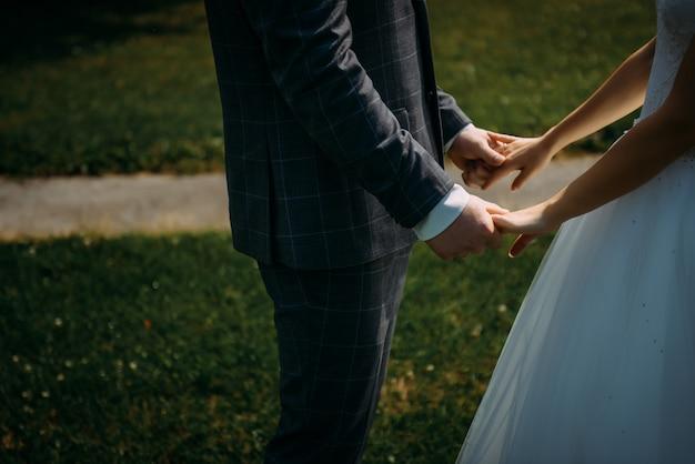 Tema di nozze, tenendosi per mano gli sposi sul fondo dell'erba verde. mani del primo piano dello sposo e della sposa. una coppia nel giorno del loro matrimonio, un momento toccante.