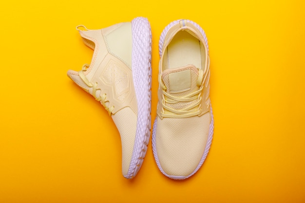 Tema di scarpe sportive in colore giallo. paia delle scarpe da tennis gialle su fondo giallo. colore estivo alla moda.