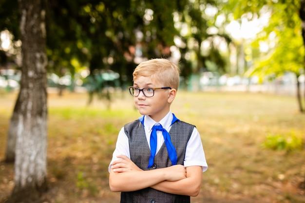 Tema educativo: ritratto di uno scolaro con grandi occhiali neri e cravatta blu. cortile della scuola, inizio delle lezioni