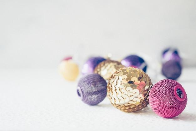 Tema festivo di vacanze di natale con la ghirlanda della palla viola rosa dorata e natale dell'oro