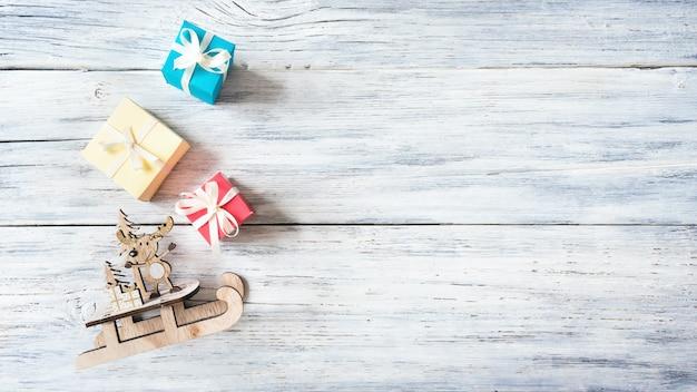 Tema festivo di vacanze di natale con la renna sveglia di legno sulla slitta, scatole regalo