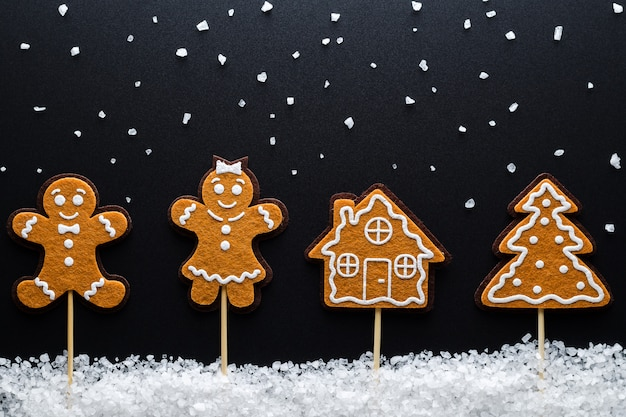 Tema natalizio. ginger men (maschio, femmina) nella neve (grande sale marino) accanto alla casa e all'albero. avvicinamento.