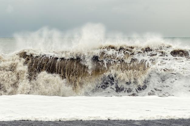 Tempesta sul mare - una grande onda con sabbia e schiuma sorge vicino alla riva.