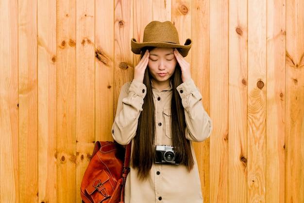 Tempie commoventi della giovane donna cinese del viaggiatore e avere mal di testa.