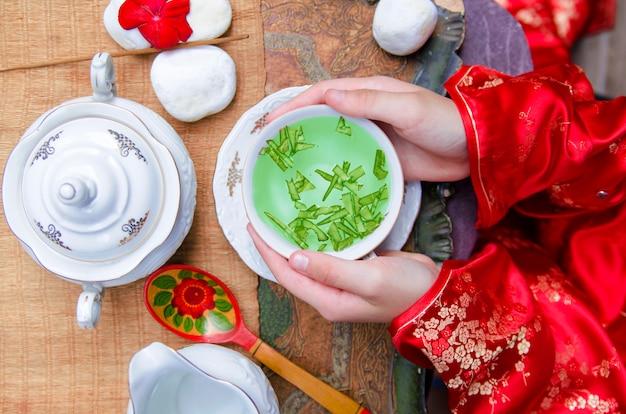 Tempo cinese del tè di festival di luna. vista superiore sulle mani della donna con la tazza di tè verde in traditiona