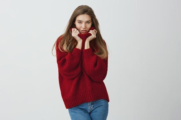 Tempo da maglione. colpo dello studio di splendido modello europeo alla moda tenendo il colletto con entrambe le mani, esprimendo sensualità, sentendosi accogliente e confortevole in abiti caldi.