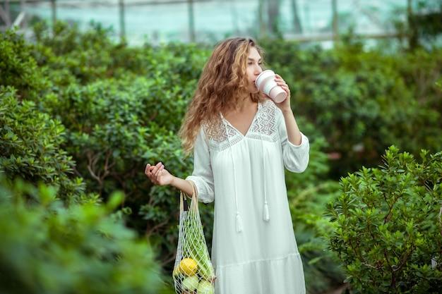 Tempo del caffè. donna in abito bianco con sacchi di verdure che bevono caffè