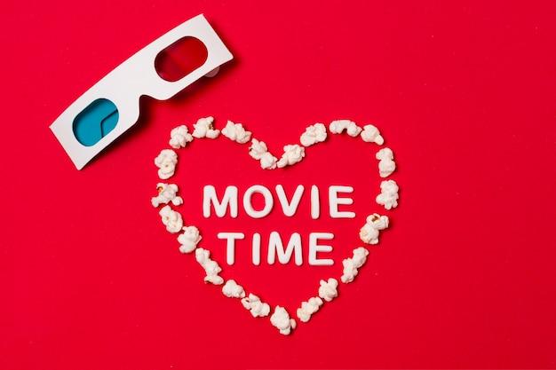 Tempo di film scritto in forma di cuore con occhiali 3d su sfondo rosso