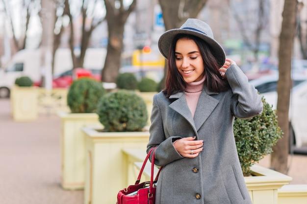 Tempo di passeggiata in città di gioiosa giovane donna alla moda in cappotto grigio, cappello che cammina sulla strada in città. sorridente, che esprime le vere emozioni positive del viso, stile di vita di lusso, prospettiva elegante.