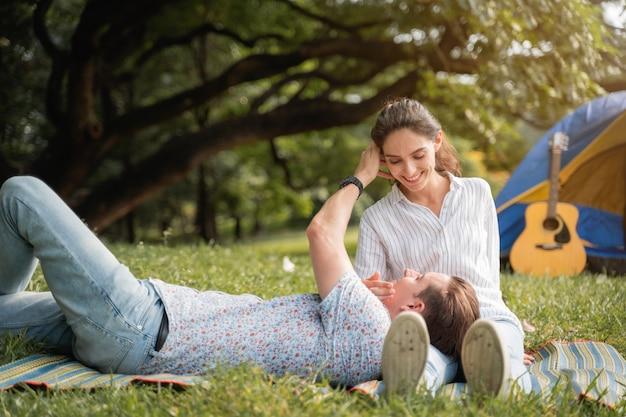 Tempo di picnic e campeggio. giovani coppie che si trovano sull'erba con la sensazione romantica. amore e tenerezza, uomo romantico che sorride alla sua ragazza, concetto di stile di vita