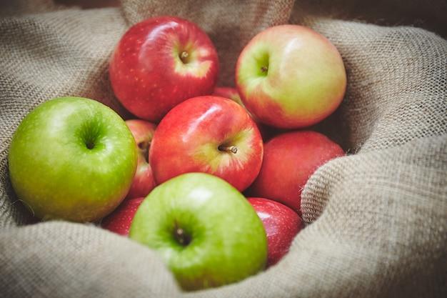 Tempo di raccolta, mele delle materie organiche dalla merce nel carrello della natura su struttura del fondo della tela di sacco
