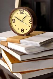 Tempo di scuola sveglia che si siede in cima ad una pila di libri. concetto di educazione