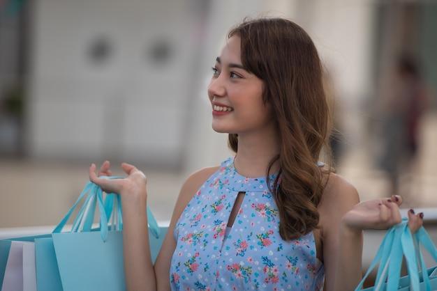 Tempo felice al concetto di compera, sacchetti della spesa asiatici della tenuta della donna al centro del centro commerciale.