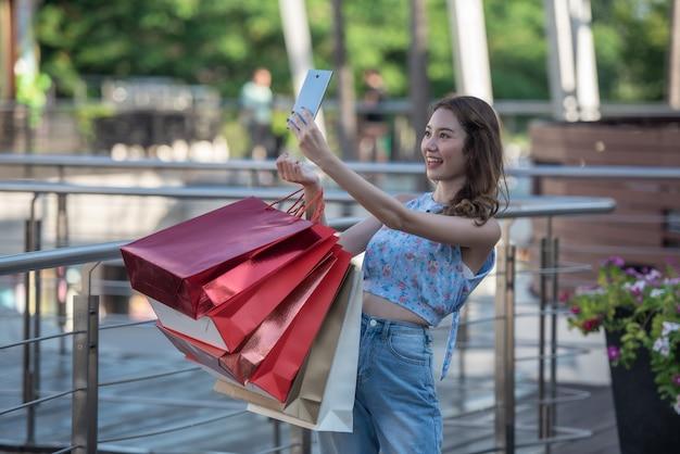 Tempo felice di comperare concetto, sacchetti della spesa asiatici della tenuta della donna e selfie lei stessa con lo smartphone in mani al centro commerciale.