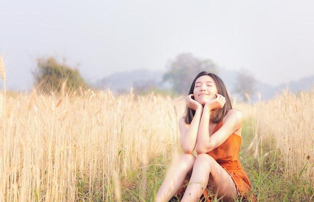 Tempo felice donna asiatica nel campo di orzo