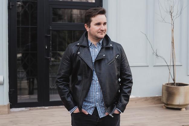 Tempo libero all'aperto. giovane uomo alla moda nel fondo urbano