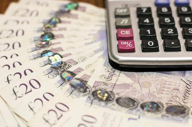Tempo per il business. vista del primo piano del calcolatore e sterline in sterline sul tavolo di legno