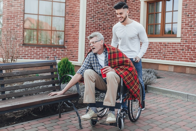 Tempo per la famiglia. il figlio aiuta suo padre più anziano sulla sedia a rotelle nel giardino di cura.
