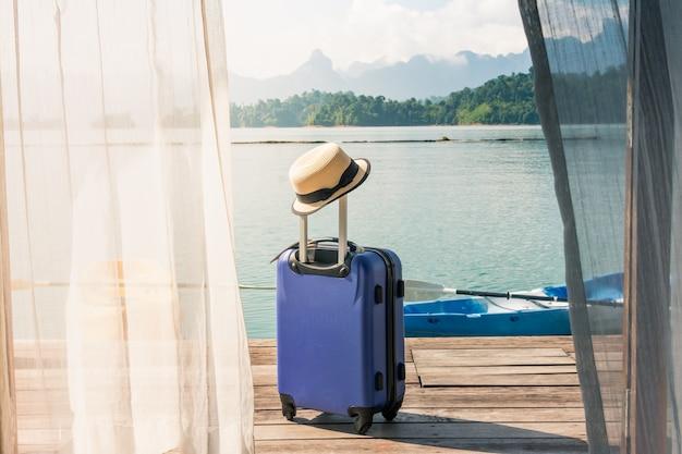 Tempo per rilassarsi, valigia in piedi sul pavimento con cappuccio fuori dalla stanza, stile di vita di viaggio.