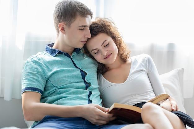 Tempo romantico le coppie caucasiche abbracciano e leggono il libro nel letto.
