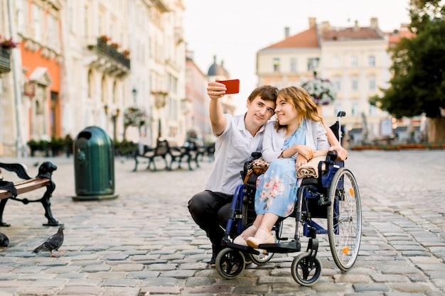 Tempo selfie. giovane felice bello che abbraccia la sua giovane donna disabile e che sorride mentre prendendo selfie con lei nella città