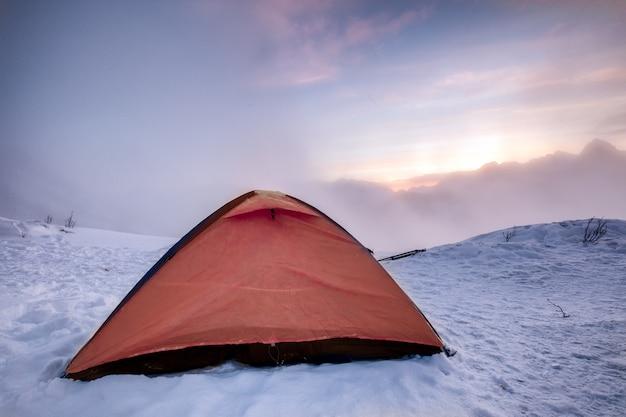 Tenda arancione di campeggio sulla collina nevosa in mattinata