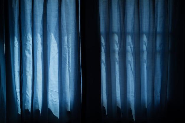 Tenda blu alla finestra, giorno di halloween nella notte sulla stanza con la finestra di orrore