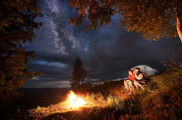 Tenda città di notte e una coppia seduta accanto al fuoco guardando in lontananza sotto il cielo della sera