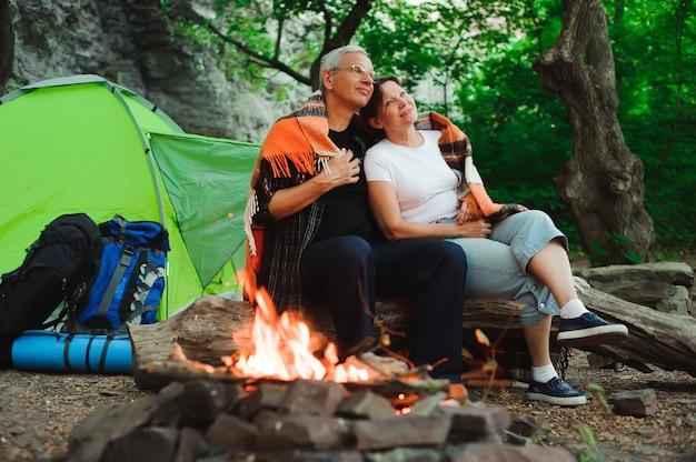 Tenda da campeggio coppia romantica seduta di notte falò