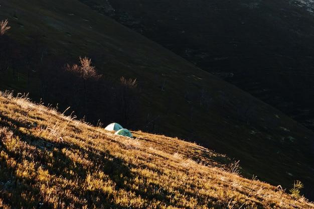 Tenda da campeggio verde del gelo due su luce solare delle montagne.