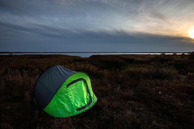 Tenda da campeggio verde sullo sfondo della natura e del lago. viaggi, turismo, campeggio.