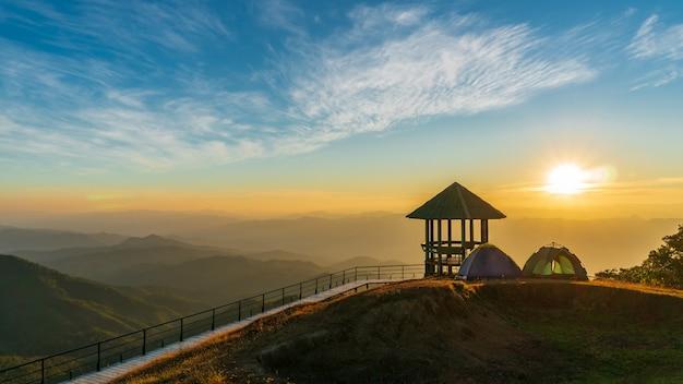 Tenda da picnic accanto al padiglione sul punto di vista e alte montagne. il sole sta cadendo in mezzo a molte montagne.