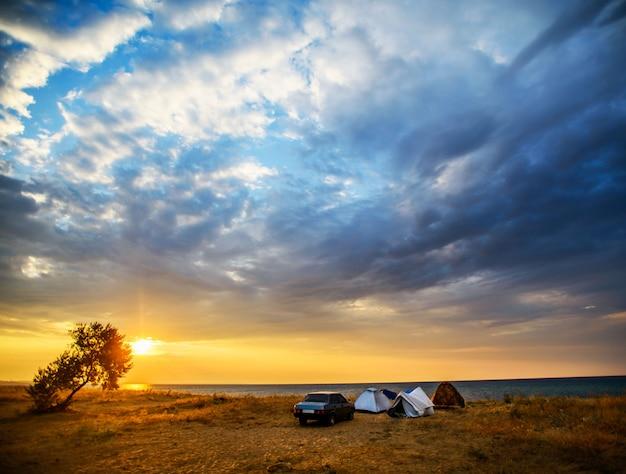 Tenda e auto sulla riva del mare