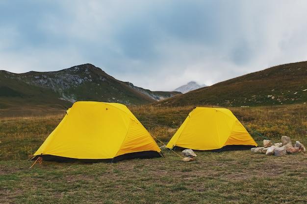 Tenda gialla due su una valle con le montagne in autunno