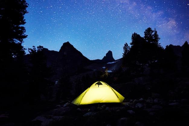 Tenda incandescente sullo sfondo del cielo stellato di notte