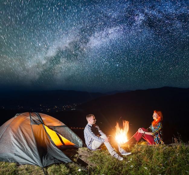Tenda notturna in campeggio. turisti delle coppie che si siedono dal fuoco di accampamento